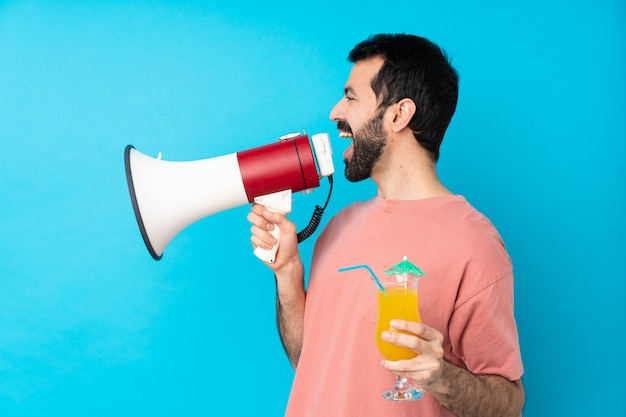 Jonge mens die over een cocktail over geïsoleerde blauwe muur houdt die door een megafoon schreeuwt
