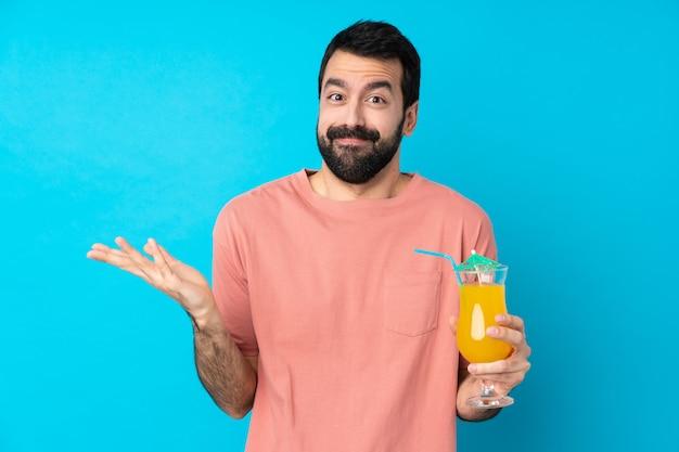 Jonge mens die over een cocktail over geïsoleerde blauwe muur houdt die twijfelgebaar maakt