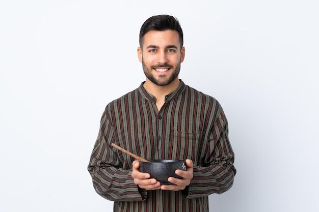 Jonge mens die over geïsoleerde muur veel glimlacht terwijl het houden van een kom noedels met eetstokjes