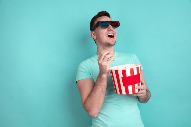 Jonge mens die popcorn op blauwe studiomuur eet