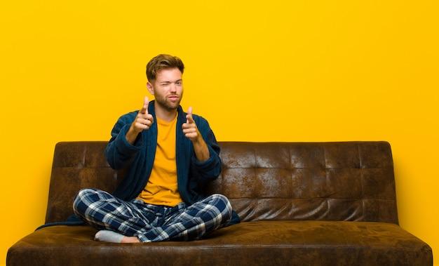Jonge mens die pyjama's draagt die gelukkig, koel, tevreden, ontspannen en succesvol voelen, op camera richten, die u kiezen. zittend op een bank