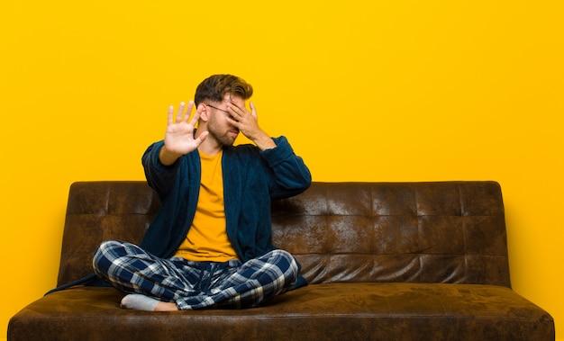 Jonge mens die pyjama's draagt die gezicht behandelen met hand en andere hand vooraan zetten om camera tegen te houden die foto's of beelden weigeren. zittend op een bank