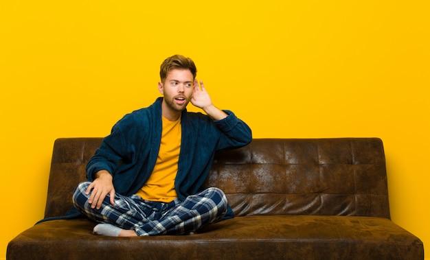 Jonge mens die pyjama's draagt die glimlachen, nieuwsgierig aan de kant kijken, proberen te roddelen of een geheim afluisteren. zittend op een bank