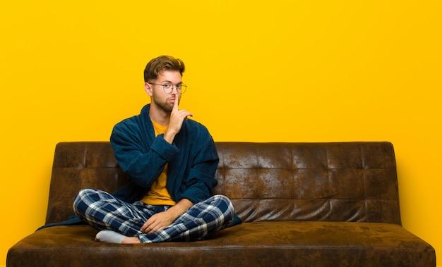 Jonge mens die pyjama's draagt die om stilte vragen en het stille gebaren met vinger die voor mond shh zeggen of een geheim houden. zittend op een bank