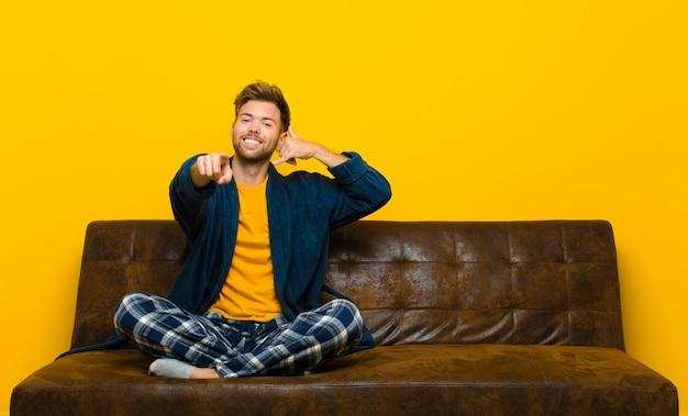 Jonge mens die pyjama's dragen die vrolijk glimlachen en aan camera richten terwijl het telefoneren u later gebaar, die op telefoon spreken. zittend op een bank