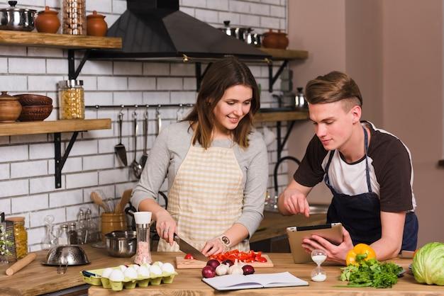 Jonge mens die recept toont aan kokend meisje