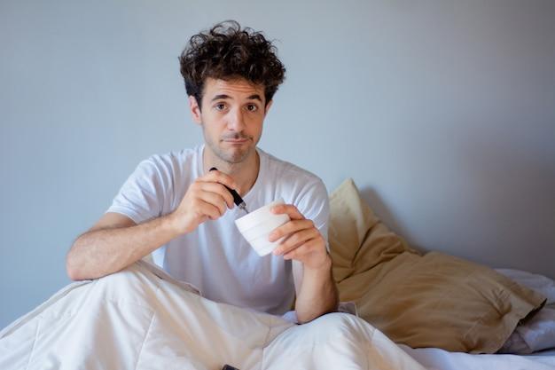 Jonge mens die roomijs in bed eet
