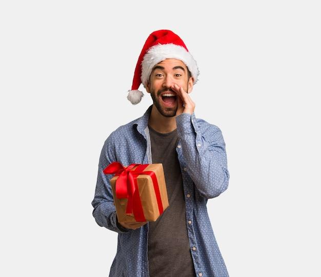 Jonge mens die santahoed draagt die iets schreeuwt gelukkig aan de voorzijde