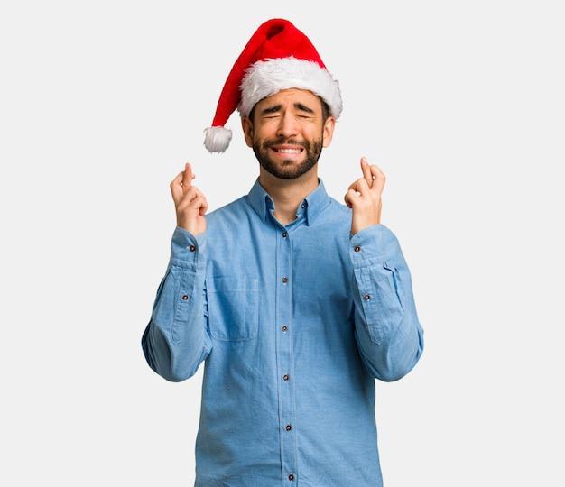 Jonge mens die santahoed draagt die vingers voor het hebben van geluk kruist