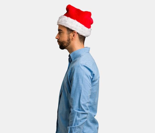Jonge mens die santahoed op de kant draagt die aan voorzijde kijkt