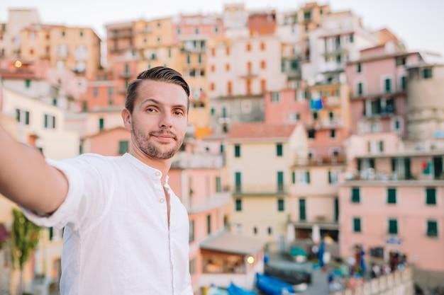 Jonge mens die selfie achtergrond mooi manarola-dorp, cinque terre, ligurië nemen