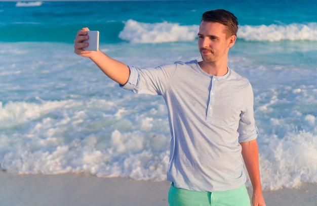 Jonge mens die selfie op de strandachtergrond het overzees nemen