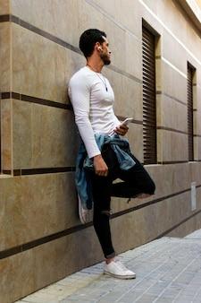 Jonge mens die smartphone en hoorzittingsmuziek in de straat kijken. lifestyle, model.