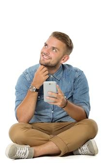 Jonge mens die terwijl het houden van een cellphone denken en op de geïsoleerde vloer zitten ,.