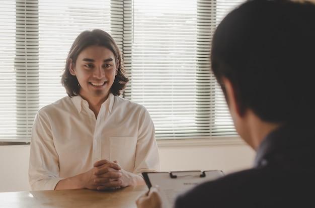 Jonge mens die tijdens baangesprek glimlachen en over zijn profiel met bedrijfs hr-managerholding het hervatten verklaren en in vergaderzaal op kantoor zitten