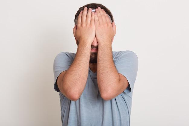 Jonge mens die toevallige grijze t-shirt dragen die zich over geïsoleerd wit met droevige uitdrukking bevinden die gezicht behandelen met beide handen