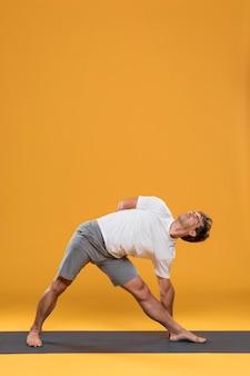 Jonge mens die uitrekkende oefening op yogamat doet