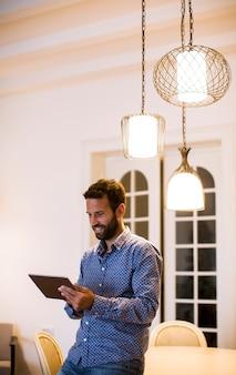 Jonge mens die van huis aan digitale tablet werkt