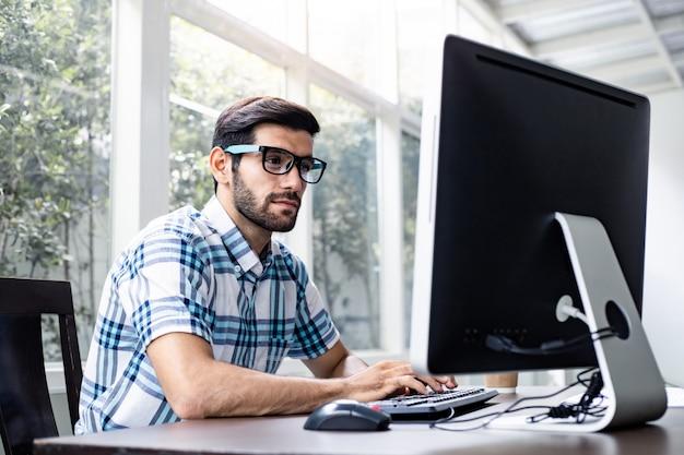 Jonge mens die van huis door computer werkt.