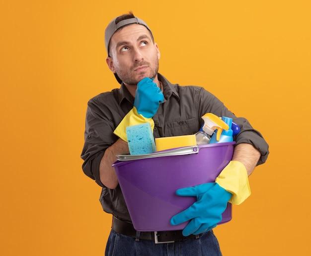 Jonge mens die vrijetijdskleding en glb in rubberhandschoenen draagt die emmer met schoonmakende hulpmiddelen houdt die omhoog met hand op kin opzoeken die zich over oranje muur bevinden