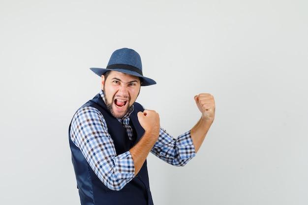 Jonge mens die winnaargebaar in overhemd, vest, hoed toont en zalig kijkt.