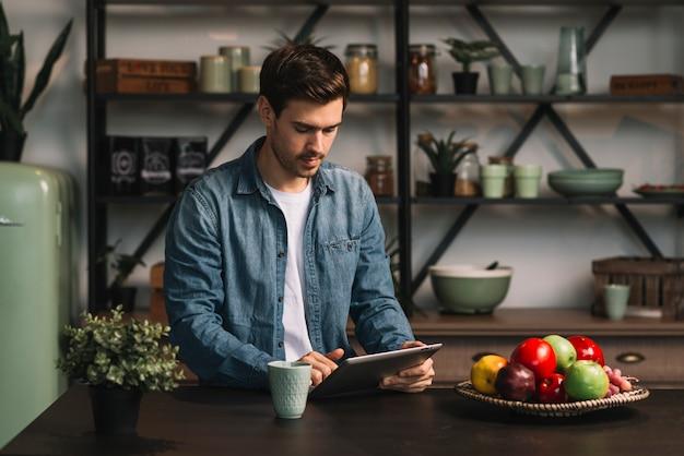 Jonge mens die zich achter de lijst bevindt die digitale tablet bekijkt