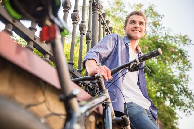 Jonge mens die zich met fiets bij de stadsstraat bevindt.