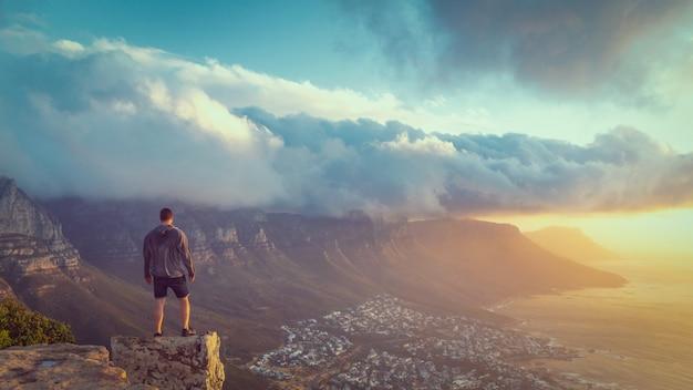 Jonge mens die zich op de rand bij de bovenkant van de hoofdberg van de leeuw in kaapstad met een mooie zonsondergangmening bevindt