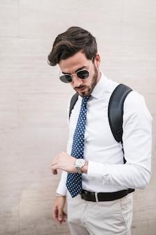 Jonge mens die zich voor muur bevindt die tijd op horloge bekijkt