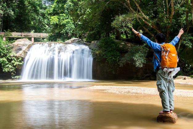 Jonge mens die zich voor waterval met hand het uitgestrekte bekijken waterval bevinden