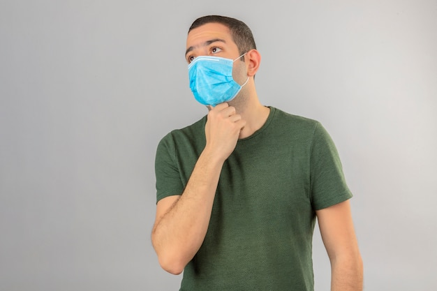 Jonge mens die ziek dragend de holdingshanden van het gezichts medische masker op zijn hals wegens keelpijn op wit wordt geïsoleerd kijken