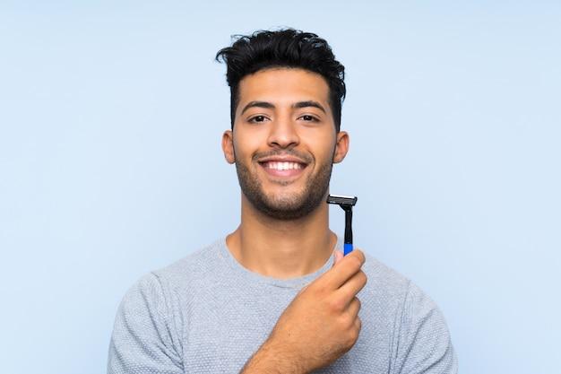 Jonge mens die zijn baard over geïsoleerde blauwe achtergrond scheert die veel glimlacht