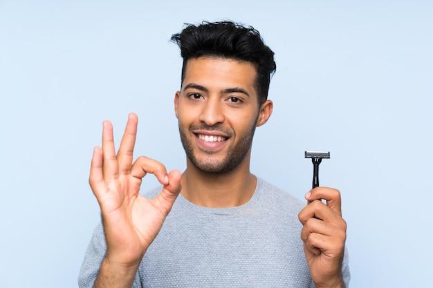 Jonge mens die zijn baard scheert die ok teken met vingers toont