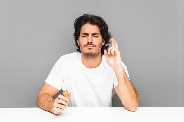 Jonge mens die zijn baard scheert die vingers kruist voor het hebben van geluk