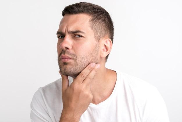 Jonge mens die zijn gezicht controleert dat zich tegen witte muur bevindt