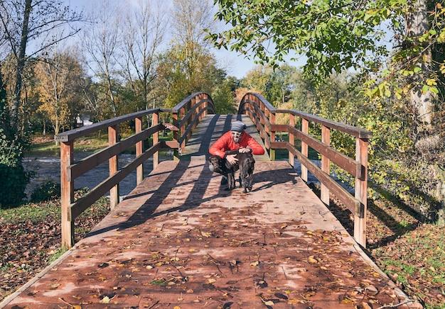 Jonge mens die zijn hond aan het eind van een houten brug op een koude de herfstochtend koestert.