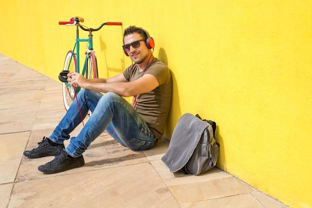Jonge mens die zonnebril draagt die op de vloer ontspant en muziek luistert. zittend tegen een gele muur met zijn computer