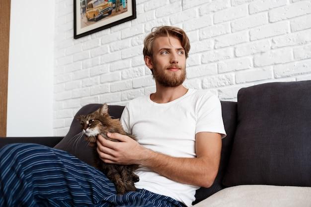 Jonge mens het glimlachen het strijken kattenzitting op bank thuis.