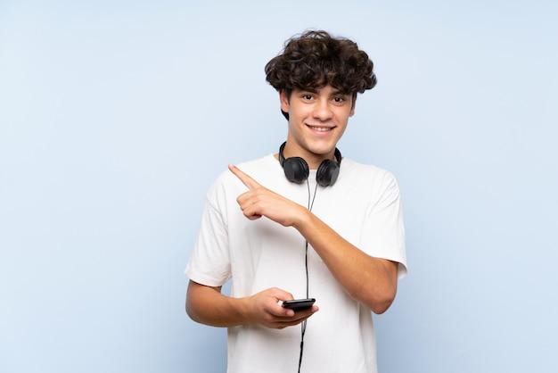 Jonge mens het luisteren muziek met mobiel over geïsoleerde blauwe muur die aan de kant richt om een product te presenteren
