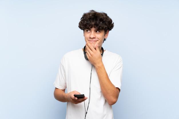 Jonge mens het luisteren muziek met mobiel over geïsoleerde blauwe muur die een idee denkt