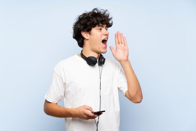 Jonge mens het luisteren muziek met mobiel over geïsoleerde blauwe muur die met wijd open mond schreeuwt