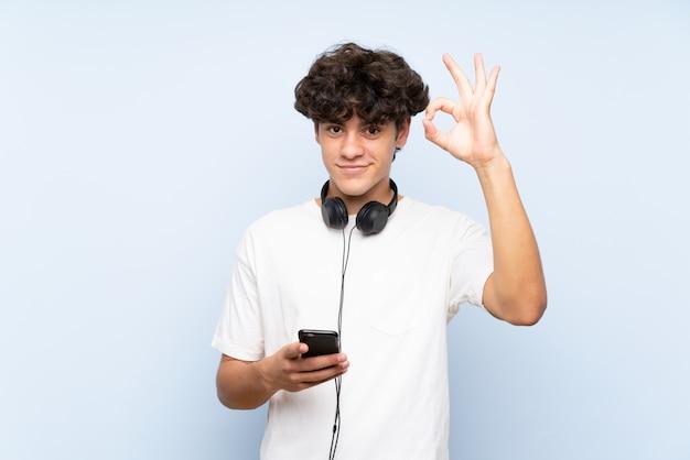 Jonge mens het luisteren muziek met mobiel over geïsoleerde blauwe muur die ok teken met vingers tonen