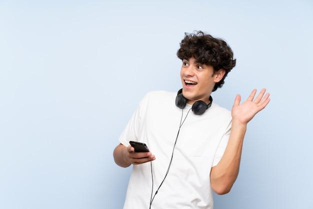 Jonge mens het luisteren muziek met mobiel over geïsoleerde blauwe muur met verrassingsgelaatsuitdrukking