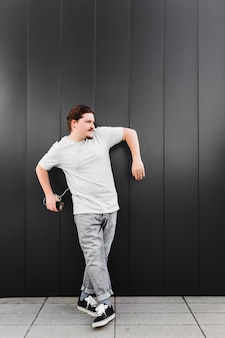Jonge mens het luisteren muziek op hoofdtelefoon door mobiele telefoon die zich tegen zwarte muur bevinden