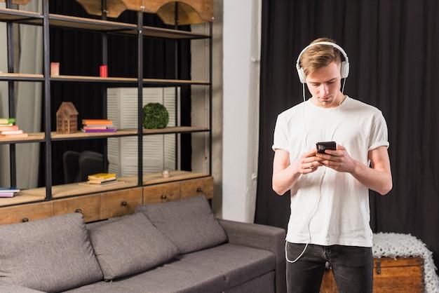 Jonge mens het luisteren muziek op hoofdtelefoon door mobiele telefoon thuis