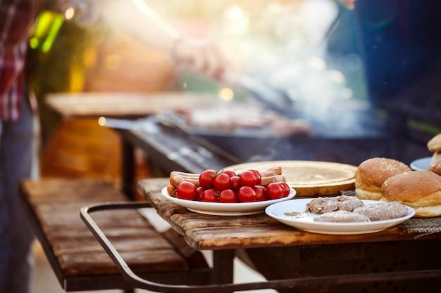 Jonge mens het roosteren barbecue bij de grill. focus op eten.