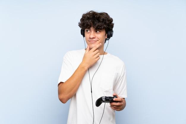 Jonge mens het spelen met een videospelletjecontrolemechanisme over geïsoleerde blauwe muur die een idee denken