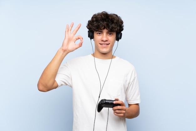Jonge mens het spelen met een videospelletjecontrolemechanisme over geïsoleerde blauwe muur die ok teken met vingers tonen
