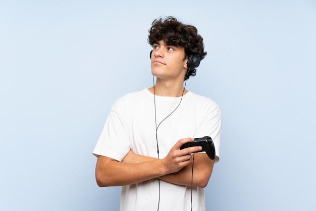 Jonge mens het spelen met een videospelletjecontrolemechanisme over geïsoleerde blauwe muur die omhoog terwijl het glimlachen kijkt