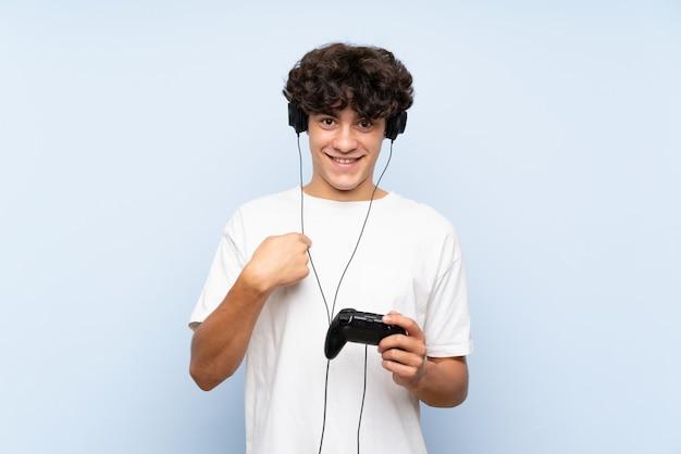 Jonge mens het spelen met een videospelletjecontrolemechanisme over geïsoleerde blauwe muur met verrassingsgelaatsuitdrukking